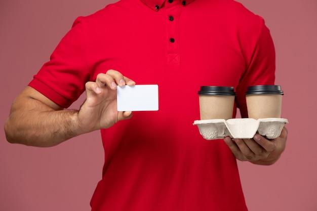Männlicher kurier der vorderansicht in der roten uniform, die braune kaffeetassen der lieferung mit weißer karte auf rosa wand hält