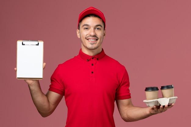 Männlicher kurier der vorderansicht in der roten uniform, die braune kaffeetassen und notizblock der lieferung auf hellrosa wandarbeiter hält