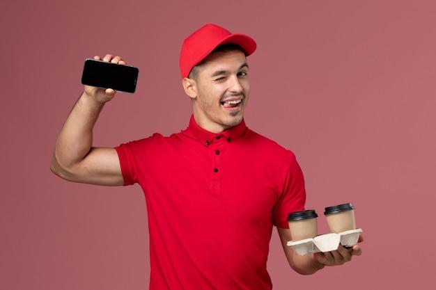 Männlicher kurier der vorderansicht in der roten uniform, die braune kaffeetassen und telefon der lieferung auf dem hellrosa wandmann hält