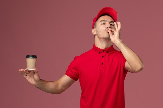 Männlicher kurier der vorderansicht in der roten uniform, die die kaffeetasse der lieferung auf dem männlichen arbeiter des rosa schreibtisches hält