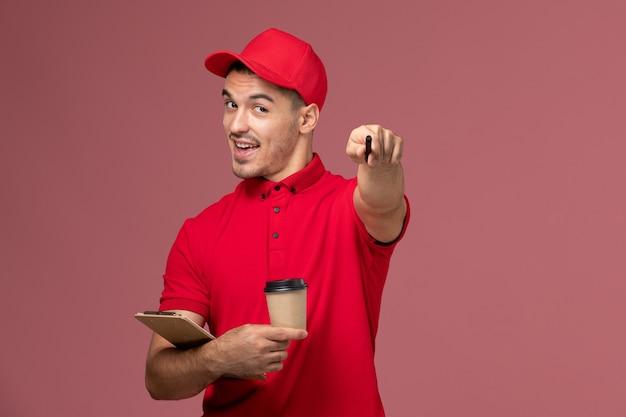 Männlicher kurier der vorderansicht in der roten uniform, die die kaffeetasse der lieferung und den notizblock auf der männlichen arbeit des rosa bodenarbeiters hält