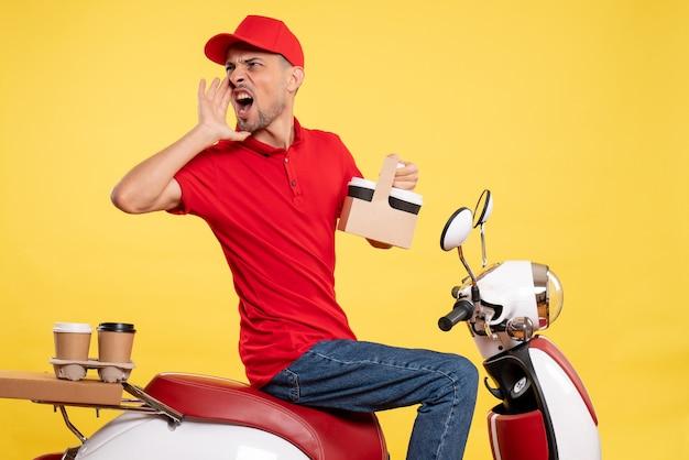 Männlicher kurier der vorderansicht in der roten uniform mit kaffee auf gelbem einheitlichem fahrradfarbarbeitsarbeitsdienstjob