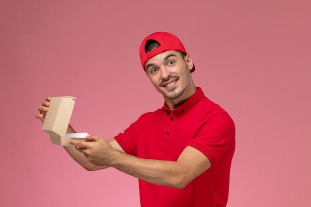 Männlicher kurier der vorderansicht in der roten uniform und im umhang, der kleines lieferpaket auf dem rosa schreibtisch hält.