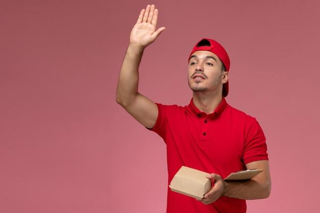 Männlicher kurier der vorderansicht in der roten uniform und im umhang, der kleines lieferpaket mit notizblock hält, der auf rosa schreibtisch winkt.