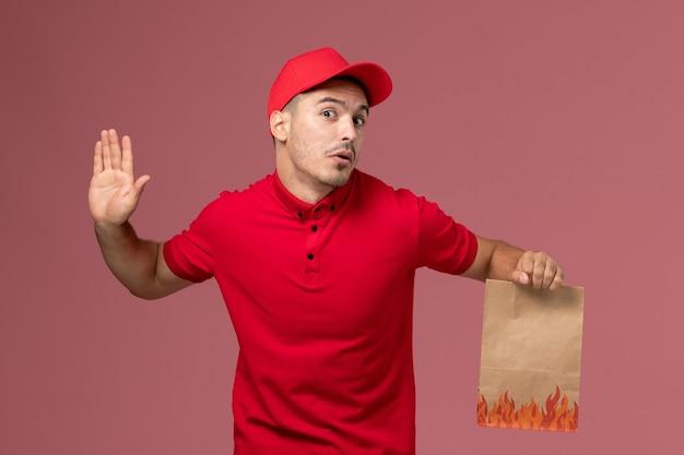 Männlicher kurier der vorderansicht in der roten uniform und im umhang, der papiernahrungsmittelpaket auf dem rosa wandarbeiter hält