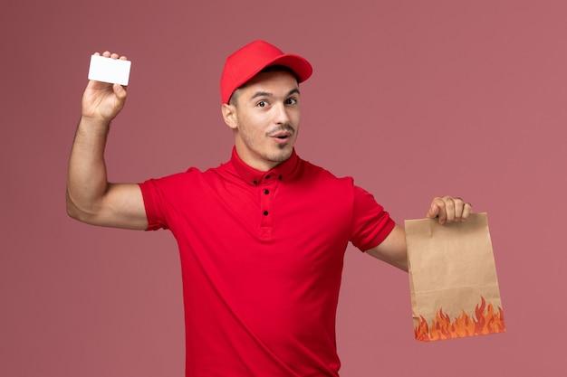 Männlicher kurier der vorderansicht in der roten uniform und im umhang, die lebensmittelpaket und karte auf der rosa wanddienstlieferuniform halten
