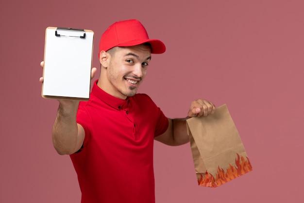 Männlicher kurier der vorderansicht in der roten uniform und im umhang, die lebensmittelpaket und notizblock halten, die auf rosa wand lächeln