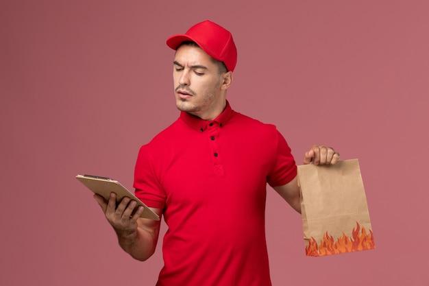 Männlicher kurier der vorderansicht in der roten uniform und im umhang, die lebensmittelverpackung und notizblock halten, die es auf rosa wand service delivery worker jobuniform lesen