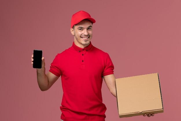 Männlicher kurier der vorderansicht in der roten uniform und im umhang, die nahrungsmittelbox zusammen mit telefon auf der männlichen lieferuniform des rosa wanddienstauftrags halten