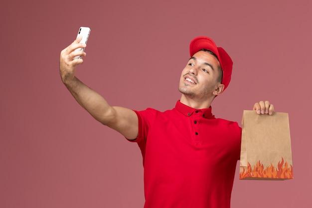 Männlicher kurier der vorderansicht in der roten uniform und im umhang, die nahrungsmittelpaket halten und selfie auf der rosa wand nehmen