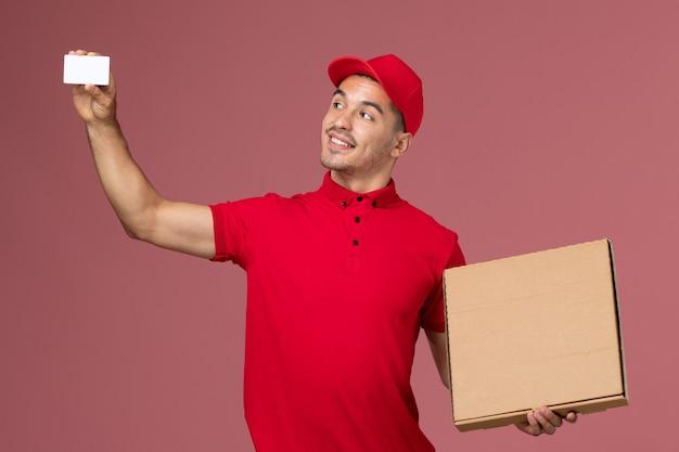 Männlicher kurier der vorderansicht in der roten uniform und im umhang, die weiße karte und nahrungsmittelbox auf der männlichen lieferuniform der rosa wanddienstaufgabe halten