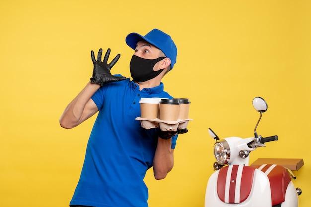 Männlicher kurier der vorderansicht in der schwarzen maske, die kaffee auf gelber arbeit lieferung job covid pandemie service uniform hält