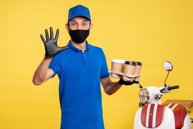 Männlicher kurier der vorderansicht in der schwarzen maske, die kaffee auf uniformarbeit der gelben job-covid-pandemie-lieferung hält