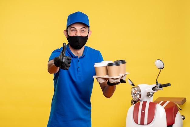 Männlicher kurier der vorderansicht in der schwarzen maske, die kaffee hält und auf gelber arbeit lieferung job covid pandemie service uniform lachen