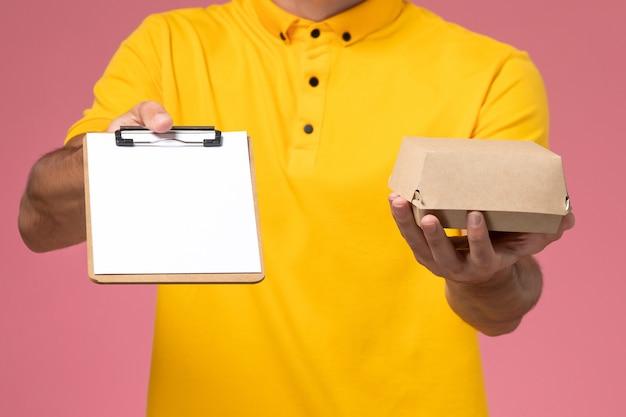 Männlicher kurier der vorderansicht in gelber uniform und mütze mit notizblock und kleinem liefernahrungsmittelpaket auf seinen händen an der hellrosa wand