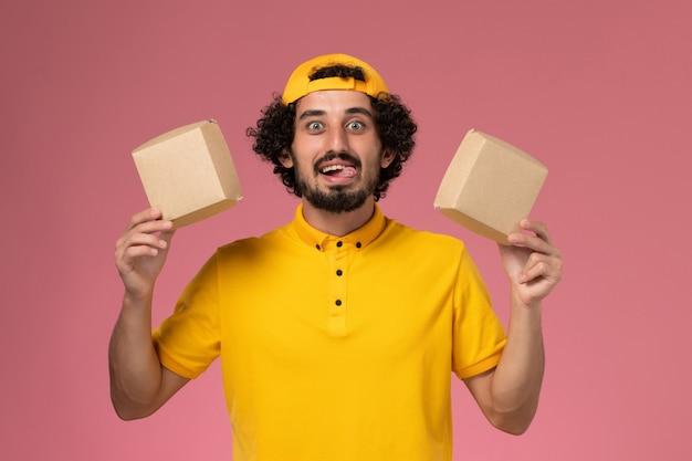 Männlicher kurier der vorderansicht in gelber uniform und umhang mit kleinen liefernahrungsmittelpaketen auf seinen händen auf dem hellrosa hintergrund.