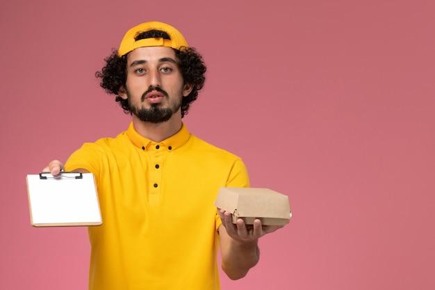 Männlicher kurier der vorderansicht in gelber uniform und umhang mit notizblock und kleinem liefernahrungsmittelpaket auf seinen händen auf dem hellrosa hintergrund.