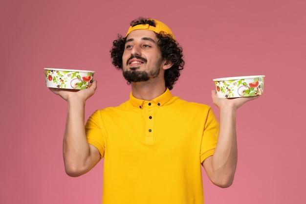 Männlicher kurier der vorderansicht in gelber uniform und umhang mit runden lieferschalen auf seinen händen auf dem hellrosa schreibtisch.