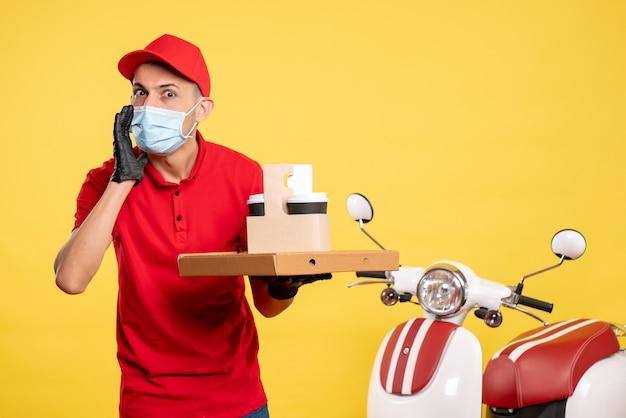 Männlicher kurier der vorderansicht in maske mit lieferkaffee und -schachtel auf der gelben farbe arbeitsservice covid-virus job uniform pandemie