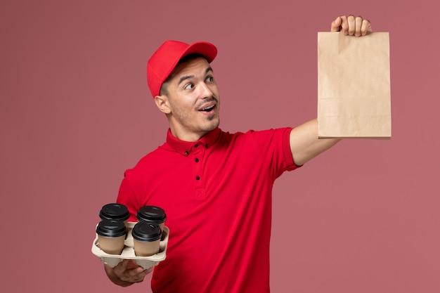 Männlicher kurier der vorderansicht in roter uniform, die braune kaffeetassen der lieferung mit lebensmittelpaket auf der rosa wanddienstlieferuniform hält