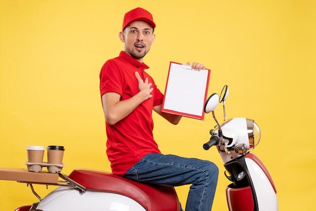 Männlicher kurier der vorderansicht in roter uniform mit aktennotiz auf gelbem farblieferfahrradarbeitsuniformarbeiterservicejob