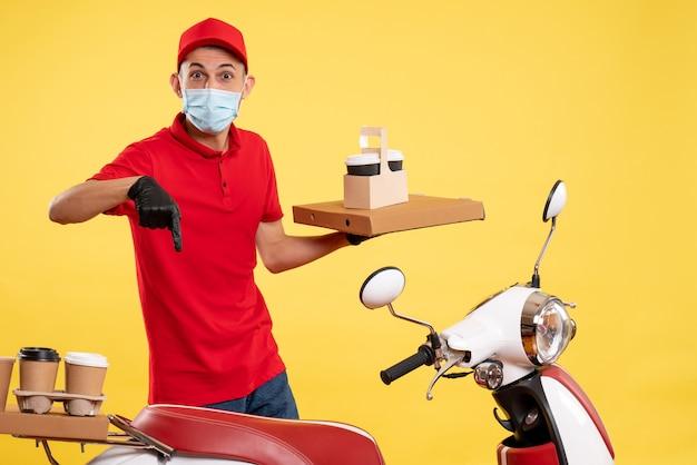 Männlicher kurier der vorderansicht in roter uniform mit lebensmittelbox und kaffee auf einem gelben pandemie-covid-uniform-virus-arbeitsdienstjob