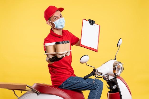 Männlicher kurier der vorderansicht in roter uniform und maske mit kaffee auf gelbem jobpandemie-lieferfarbkovid-arbeitsnahrungsmittel