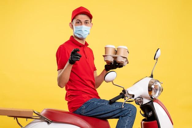 Männlicher kurier der vorderansicht in uniform und maske mit kaffee auf gelber dienstfarbpandemie-covid-virus-arbeit