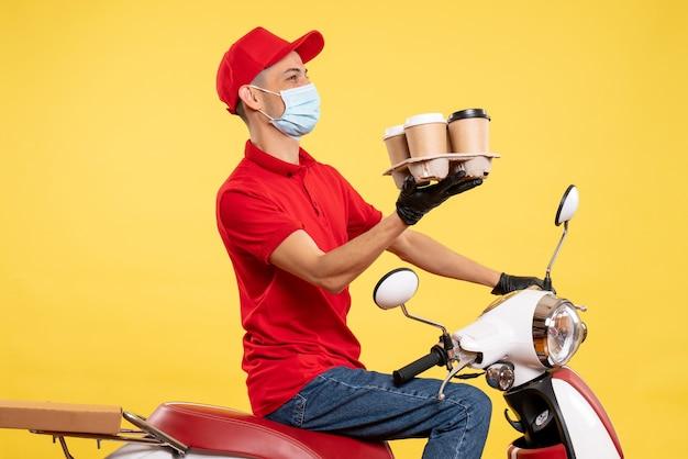 Männlicher kurier der vorderansicht in uniform und maske mit kaffee auf gelber food-service-job-pandemie-covid-virus-arbeitsfarbe