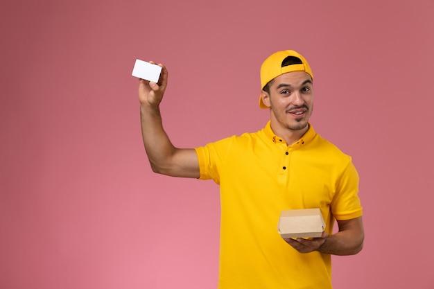 Männlicher kurier der vorderansichtansicht in der gelben uniform, die karte und kleines nahrungsmittelpaket auf rosa wand hält
