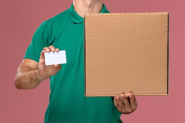 Männlicher kurier der vorderansichtansicht in der grünen uniform, die nahrungsmittelbox mit weißer karte auf rosa hintergrund hält
