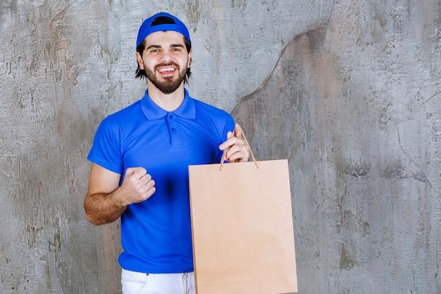 Männlicher kurier in blauer uniform, der eine einkaufstüte aus pappe hält und ein positives handzeichen zeigt
