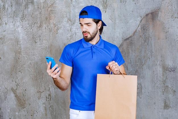 Männlicher kurier in blauer uniform, der eine einkaufstüte aus pappe hält und mit dem telefon spricht.