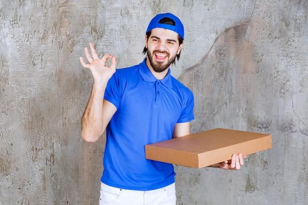 Männlicher kurier in blauer uniform, der eine pappschachtel zum mitnehmen trägt und ein positives handzeichen zeigt.