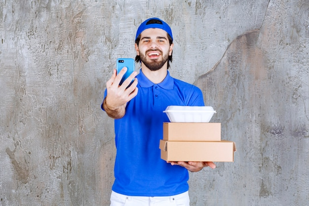 Männlicher kurier in blauer uniform, der karton- und plastikkisten trägt und neue bestellungen per smartphone entgegennimmt