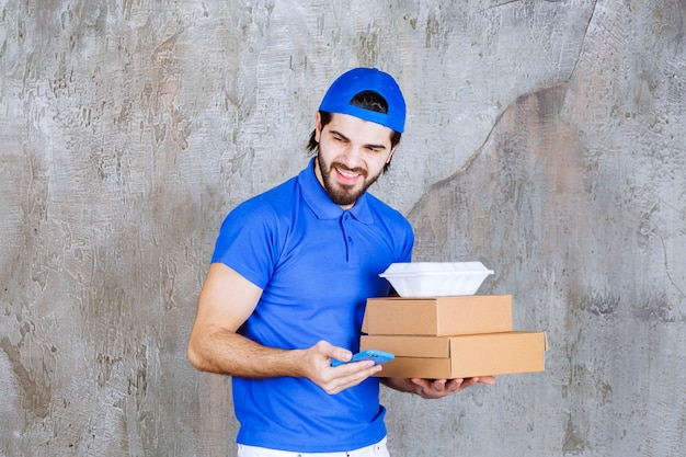 Männlicher kurier in blauer uniform, der karton- und plastikkisten trägt und neue bestellungen per smartphone entgegennimmt.
