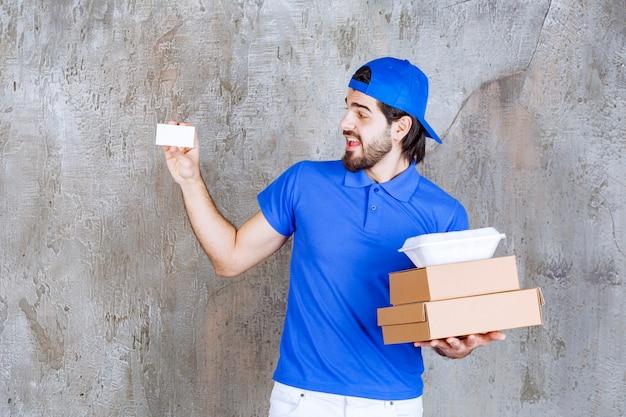 Männlicher kurier in blauer uniform, der karton- und plastikkisten trägt und seine visitenkarte vorlegt