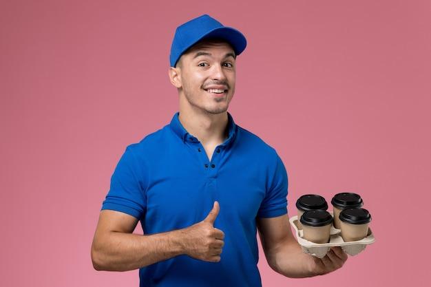 Männlicher kurier in blauer uniform, die kaffeetassen mit leichtem lächeln auf rosa, arbeiteruniform-servicebereitstellung hält