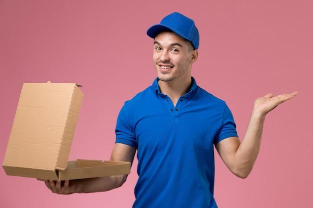 Männlicher kurier in blauer uniform, die lebensmittelbox hält, die es auf rosa, einheitlicher dienstauftragslieferung öffnet