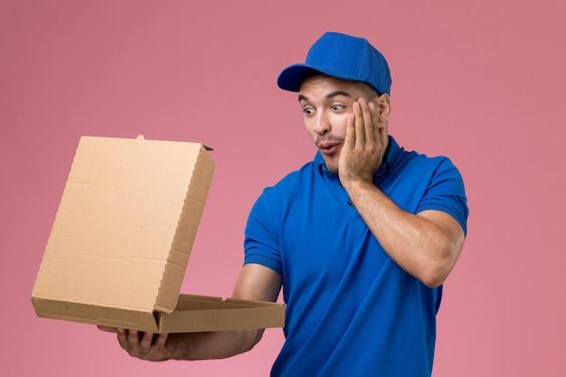 Männlicher kurier in blauer uniform, die lebensmittelbox hält, die es auf rosa, einheitlicher dienstauftragslieferung schockiert öffnet