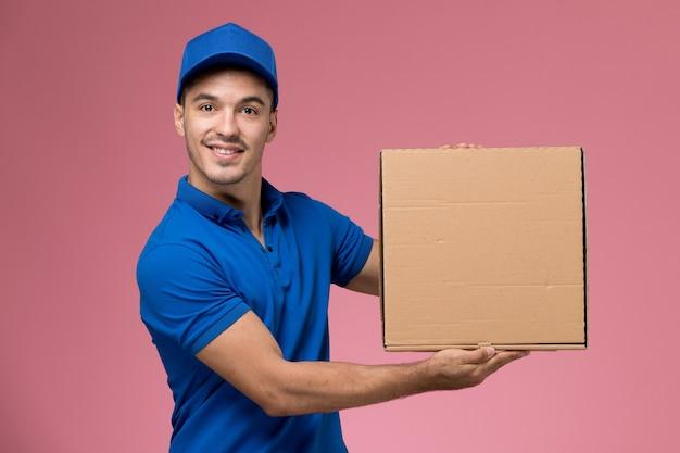 Männlicher kurier in blauer uniform, die lieferbox des essens auf rosa, arbeiteruniform-dienstlieferung hält