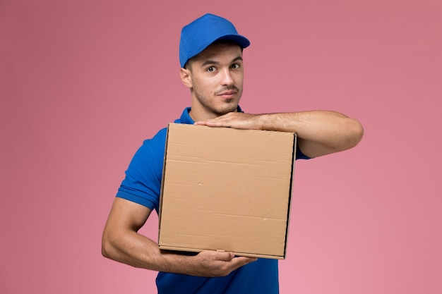 Männlicher kurier in blauer uniform, die lieferbox des essens hält, das mit ihm auf rosa, dienstarbeiteruniformdienstlieferung aufwirft
