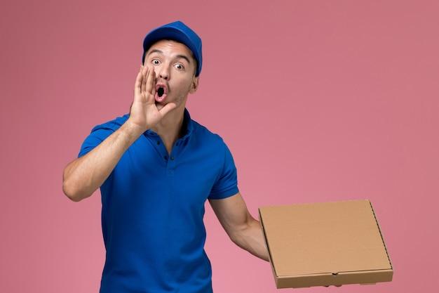 Männlicher kurier in blauer uniform, die lieferbox des essens hält und auf rosa, arbeiteruniform-dienstlieferung schreit