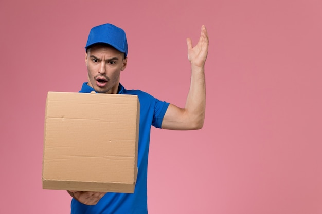 Männlicher kurier in blauer uniform, die lieferbox des lebensmittels hält, das es auf rosa, einheitlicher servicezustellung öffnet