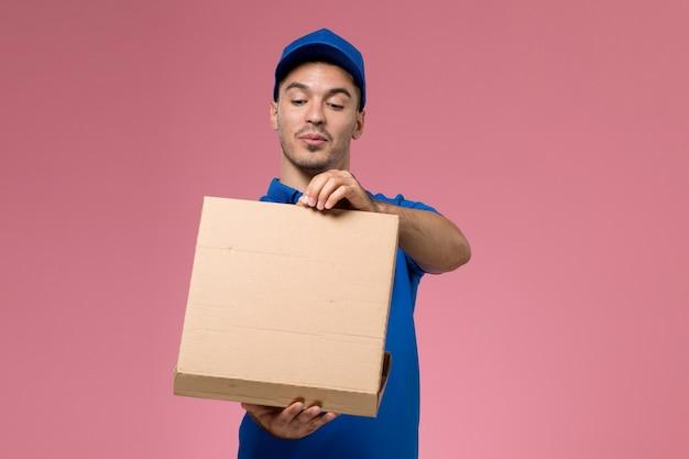 Männlicher kurier in blauer uniform, die lieferbox des lebensmittels hält und auf rosa, arbeiteruniform-dienstlieferung öffnet