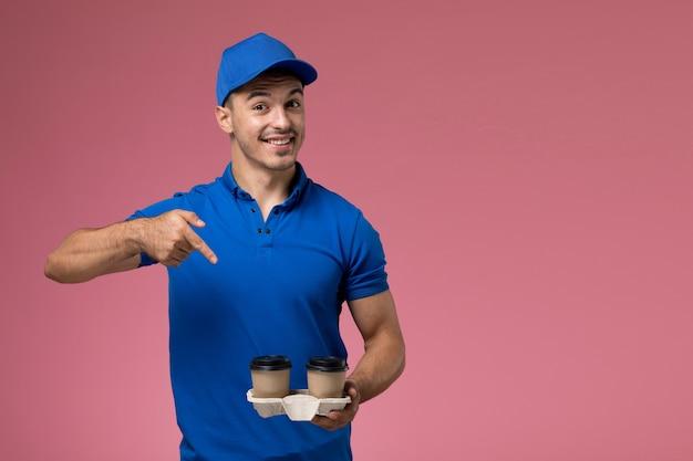 Männlicher kurier in blauer uniform, die lieferkaffeetassen mit lächeln auf rosa, einheitlicher jobarbeiterdienstlieferung hält