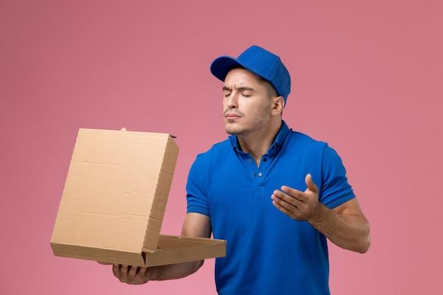 Männlicher kurier in blauer uniform, die lieferung food box hält, riecht es auf rosa, einheitliche arbeit arbeiter service lieferung