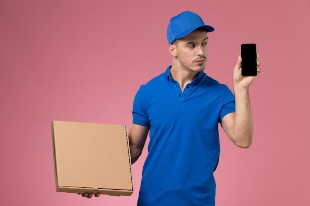 Männlicher kurier in blauer uniform, die lieferung food-box-telefon auf rosa, einheitlicher jobarbeiter-service-lieferung hält