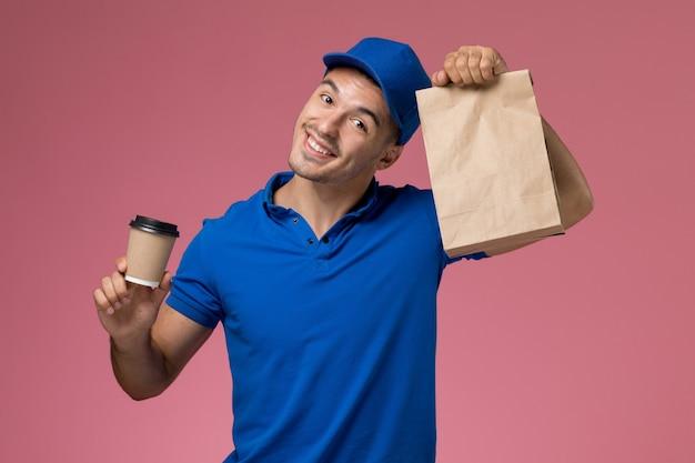 Männlicher kurier in blauer uniform, die lieferung kaffeetasse-lebensmittelpaket auf rosa, einheitlicher servicejobzustellung hält