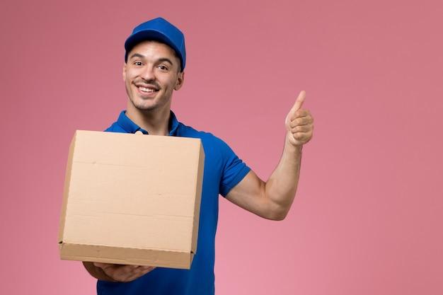 Männlicher kurier in blauer uniform, die nahrungsmittelbox auf rosa, dienstarbeiteruniformdienstlieferung hält